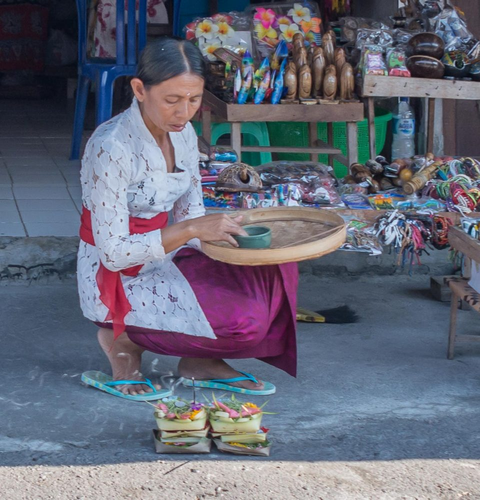 Balinese woman perform Sembahyang (Puja in India) with offerings (called Canang Sari) in her shop