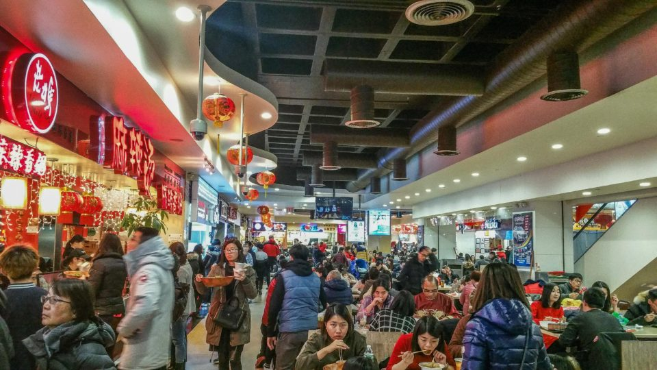 Food Court in New World Mall, Chinatown, Flushing, NYC decorated in bright red colors and lanterns.